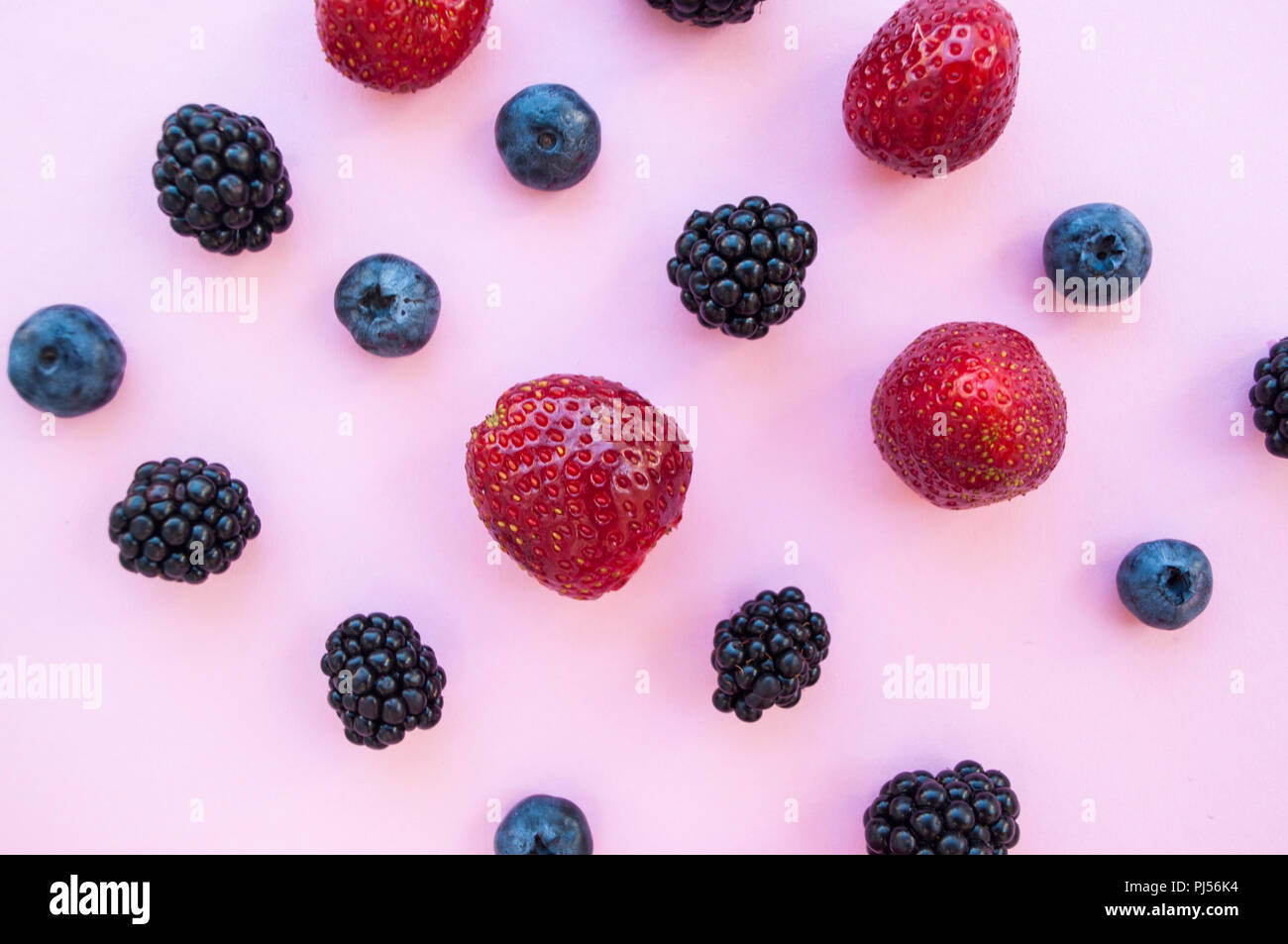 Flat lay of berries on pastel colored background. - Stock Image