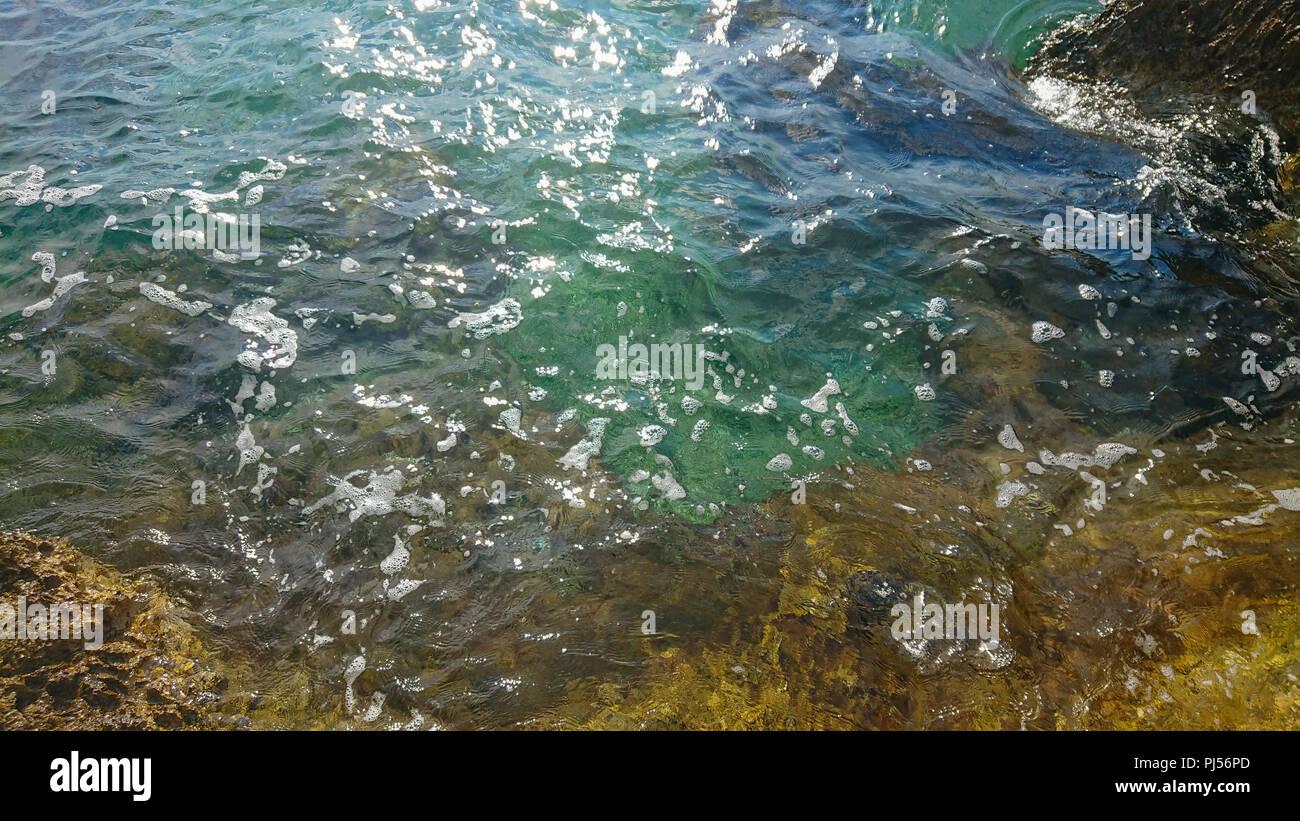 Rocky beach, bue transparent sea - Stock Image