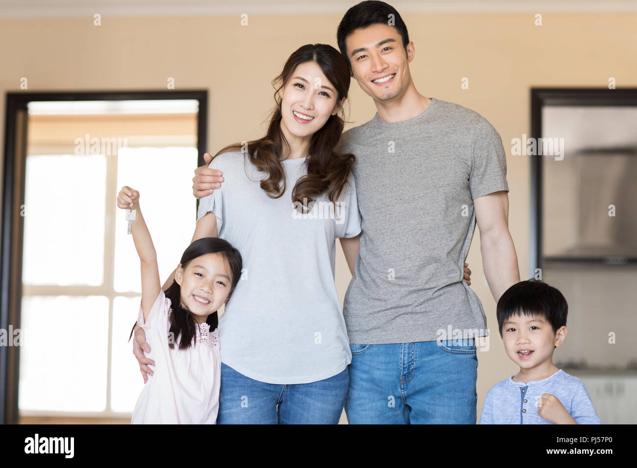 16b88d2738d Happy young family holding keys in their new house Stock Photo ...