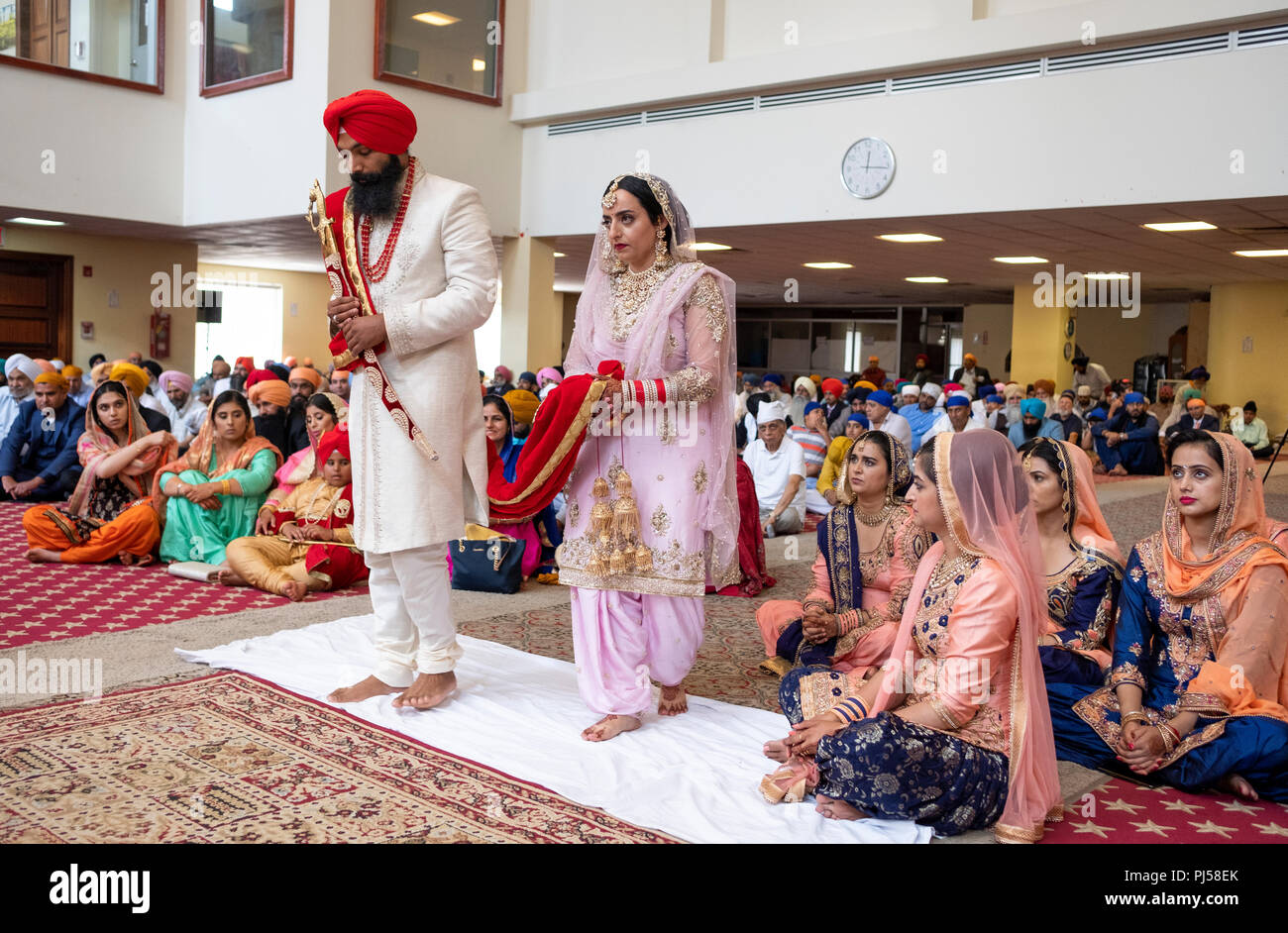 A Sikh bride and groom in a temple during their wedding ceremony. In Queens, New York City Stock Photo