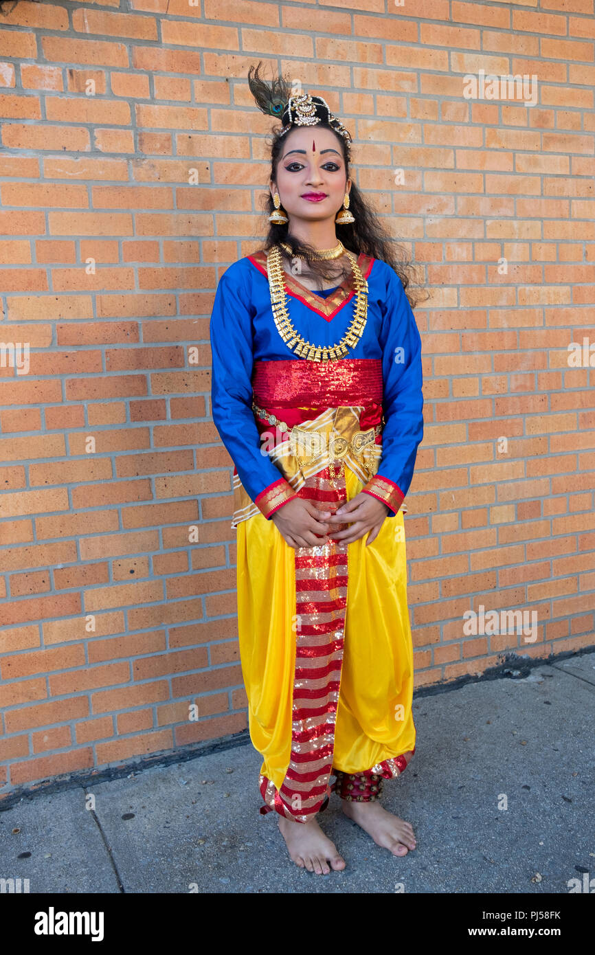 A pretty teenager in a traditional Indian costume poses for a photo on Janamashthmi prior to her performing at a holiday block party. In Queens, NY. - Stock Image