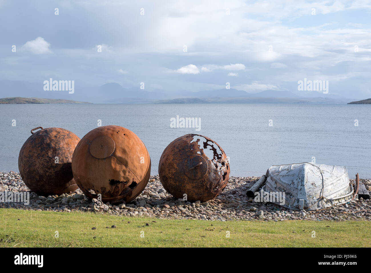 Rusty buoys on the beach at Polbain, north of Ullapool, on the west coast of Scotland. Summer Isles in the background - Stock Image