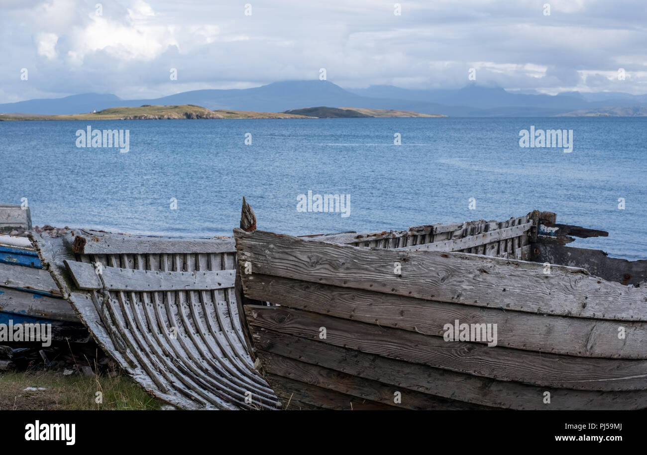 Ruins of small boat on beach at Polbain, north of Ullapool. In background, view of the Summer Isles taken from mainland on the west coast of Scotland. - Stock Image