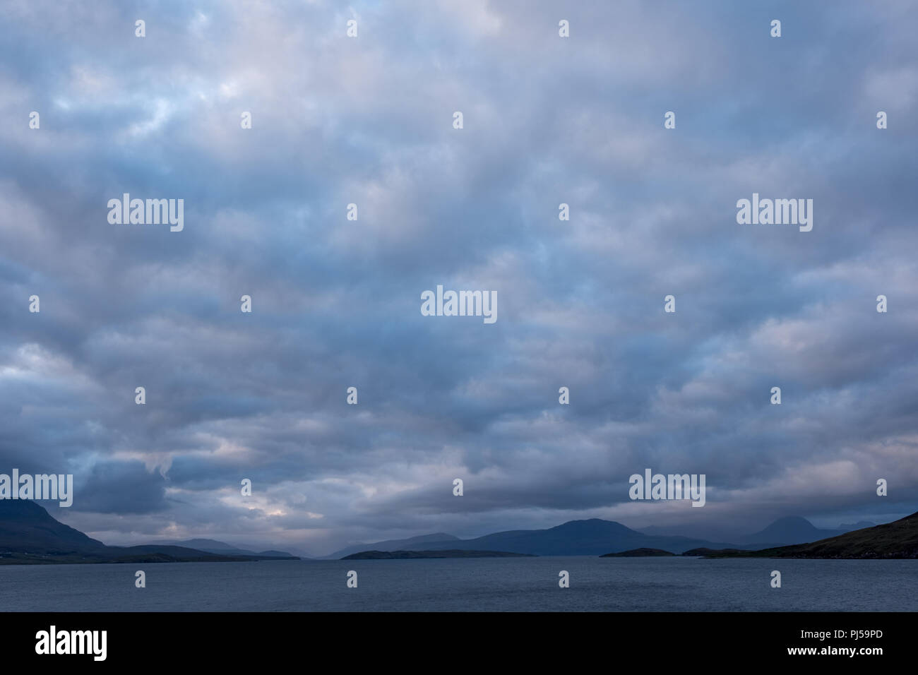 The Summer Isles at dusk (blue hour), photographed from the UK mainland, north of Ullapool on the west coast of Scotland Rocky outcrop in foreground. - Stock Image