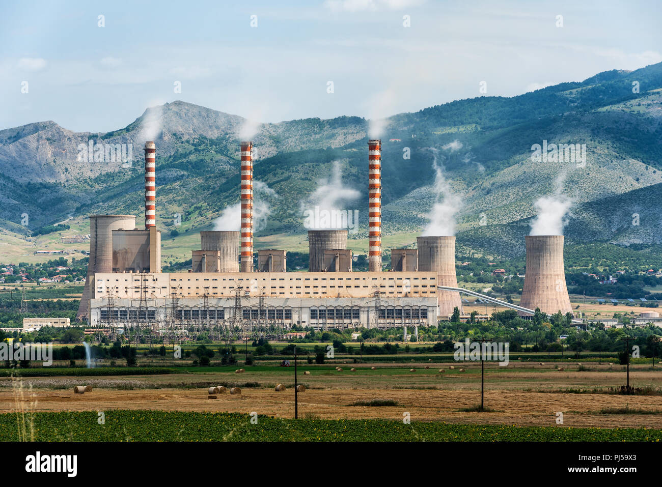 Factory chimneys smoke rising into the sky between wheat field and the hills - Stock Image