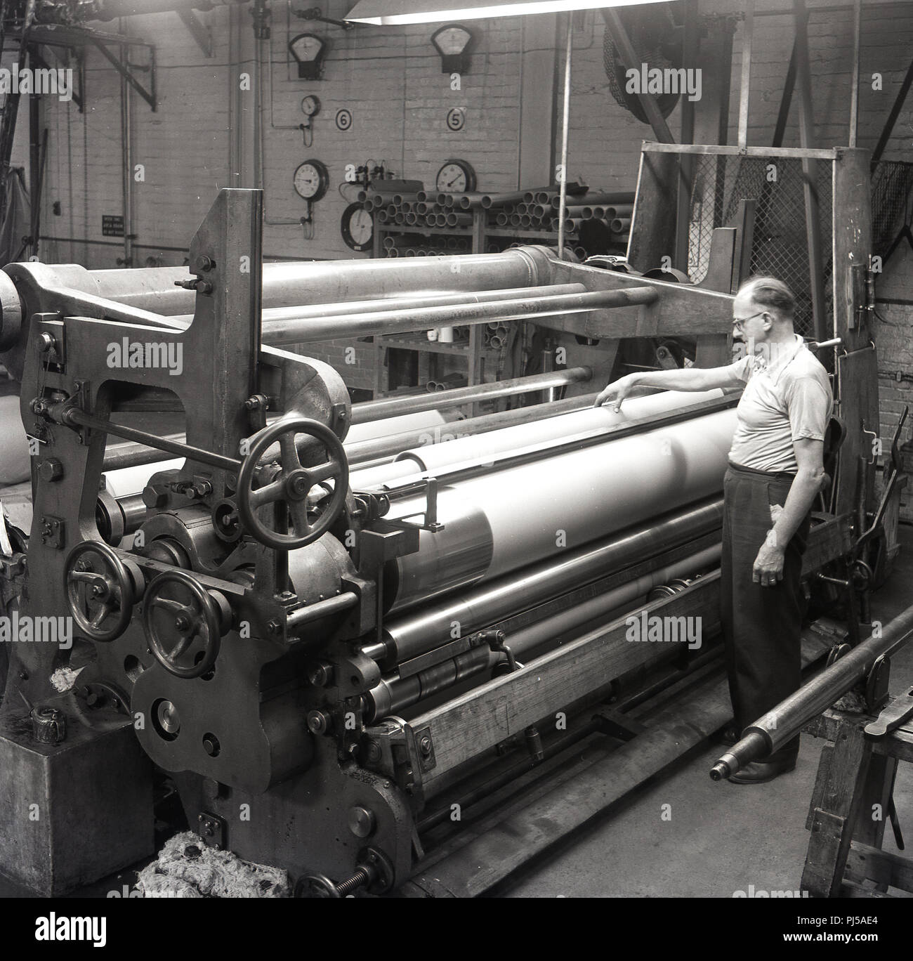 1950s, historical, At the Brittains paper mill, a male worker oversees a large paper press machine using large steel rollers or 'calender rolls' to produce a paper with a smooth finish, England, UK. - Stock Image