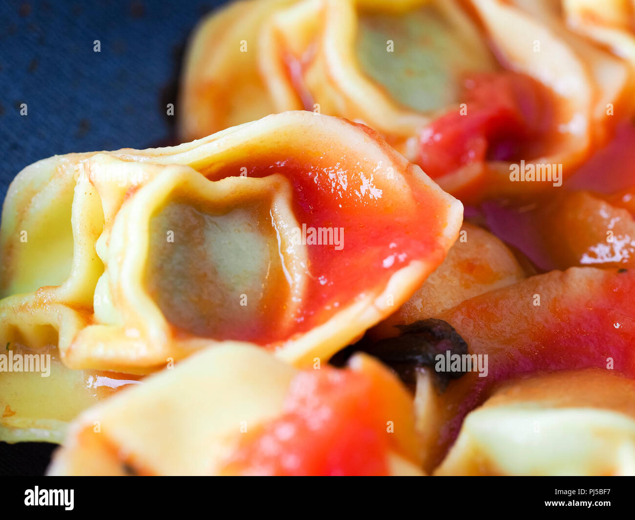 Cooking lunch at home, spinach and ricotta cheese tortellini stuffed italian pasta with tomato pomodoro sauce - Stock Image