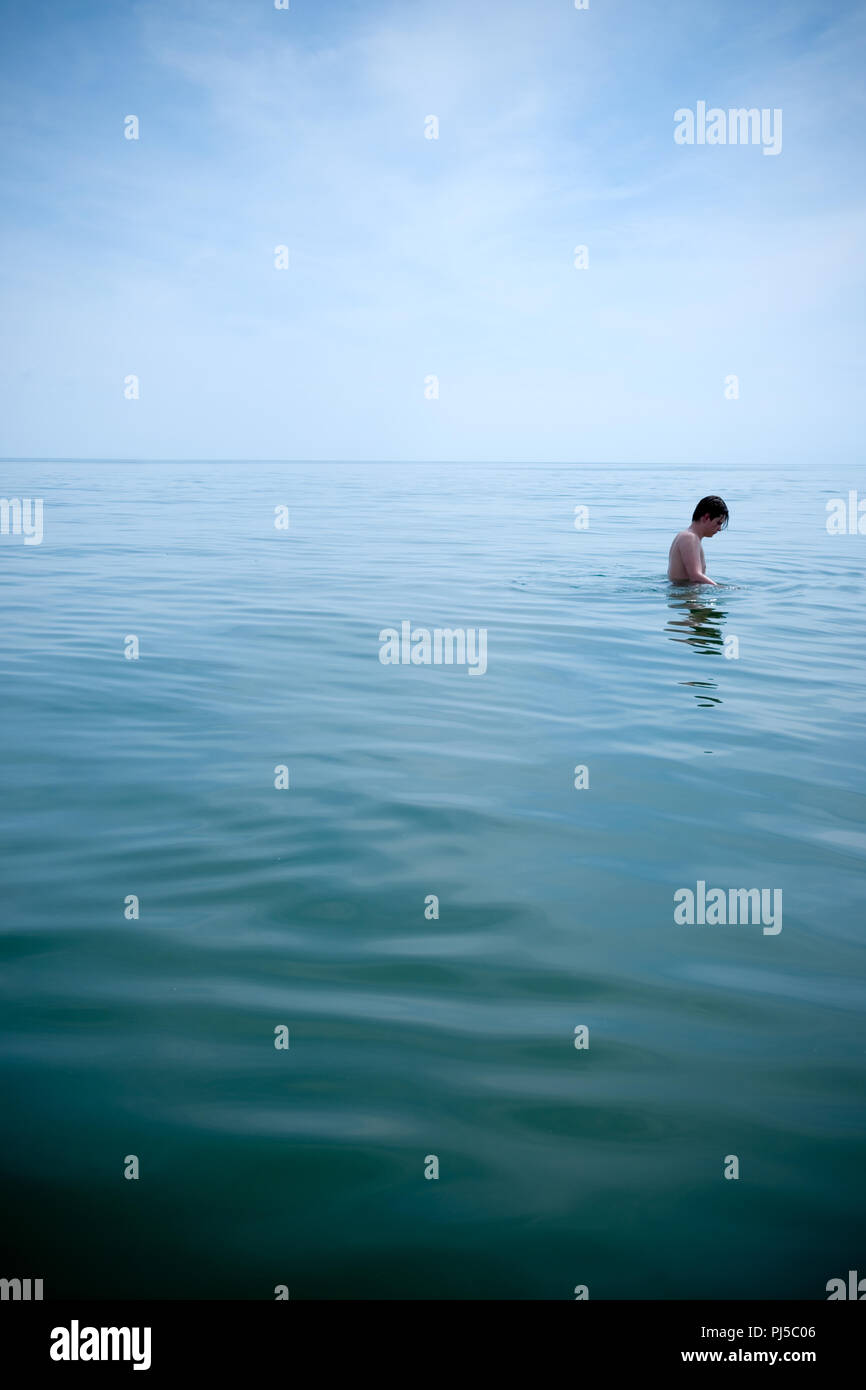 dreamy photograph of male teenager all alone and up to his waist in a very calm sea on a slightly overcast day in the french mediterranean - Stock Image