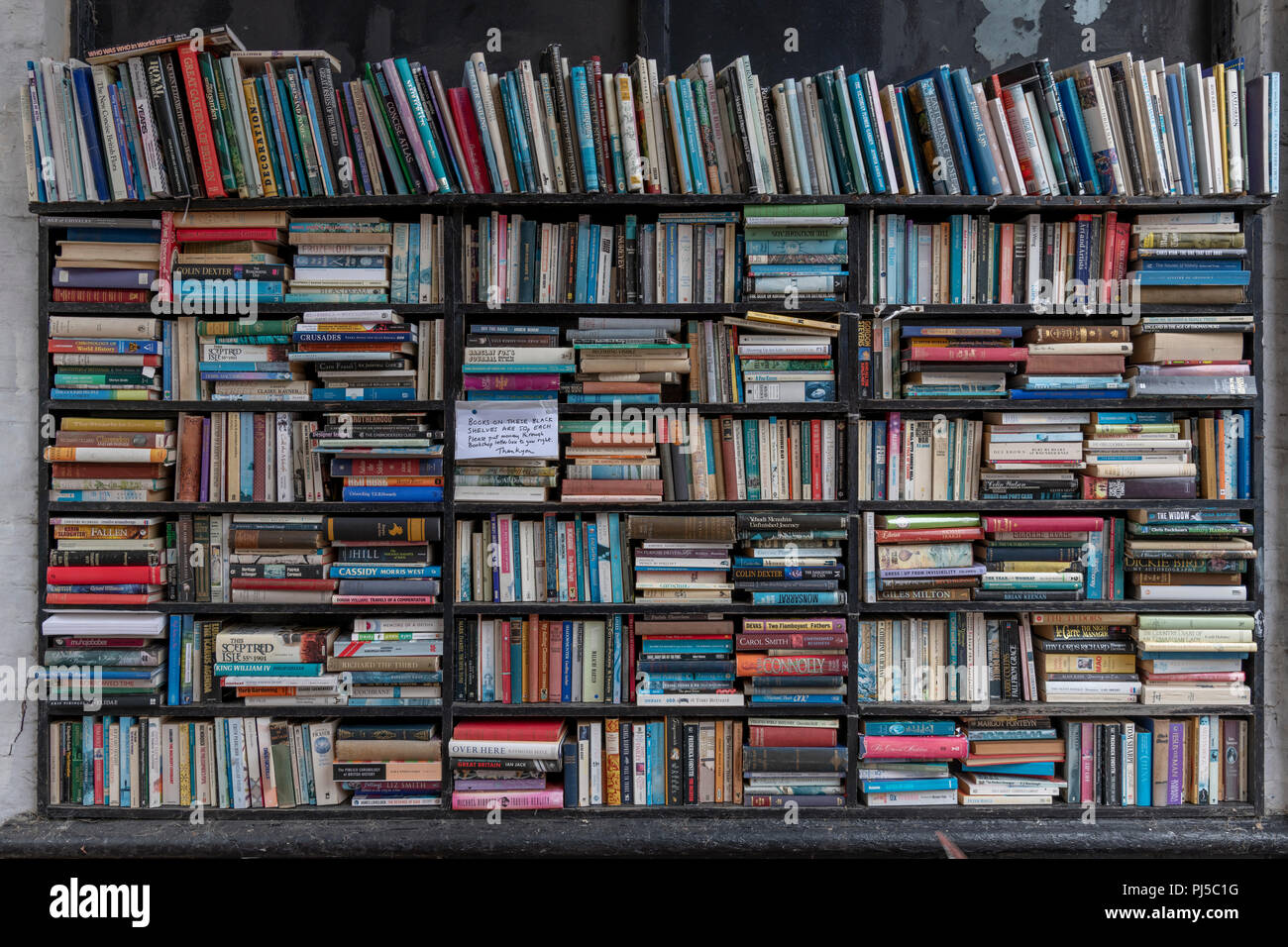 Honesty bookshelves outside a bookshop in Eastbourne. Anyone buying a book has to post the cash through the letterbox when the shop is closed. - Stock Image