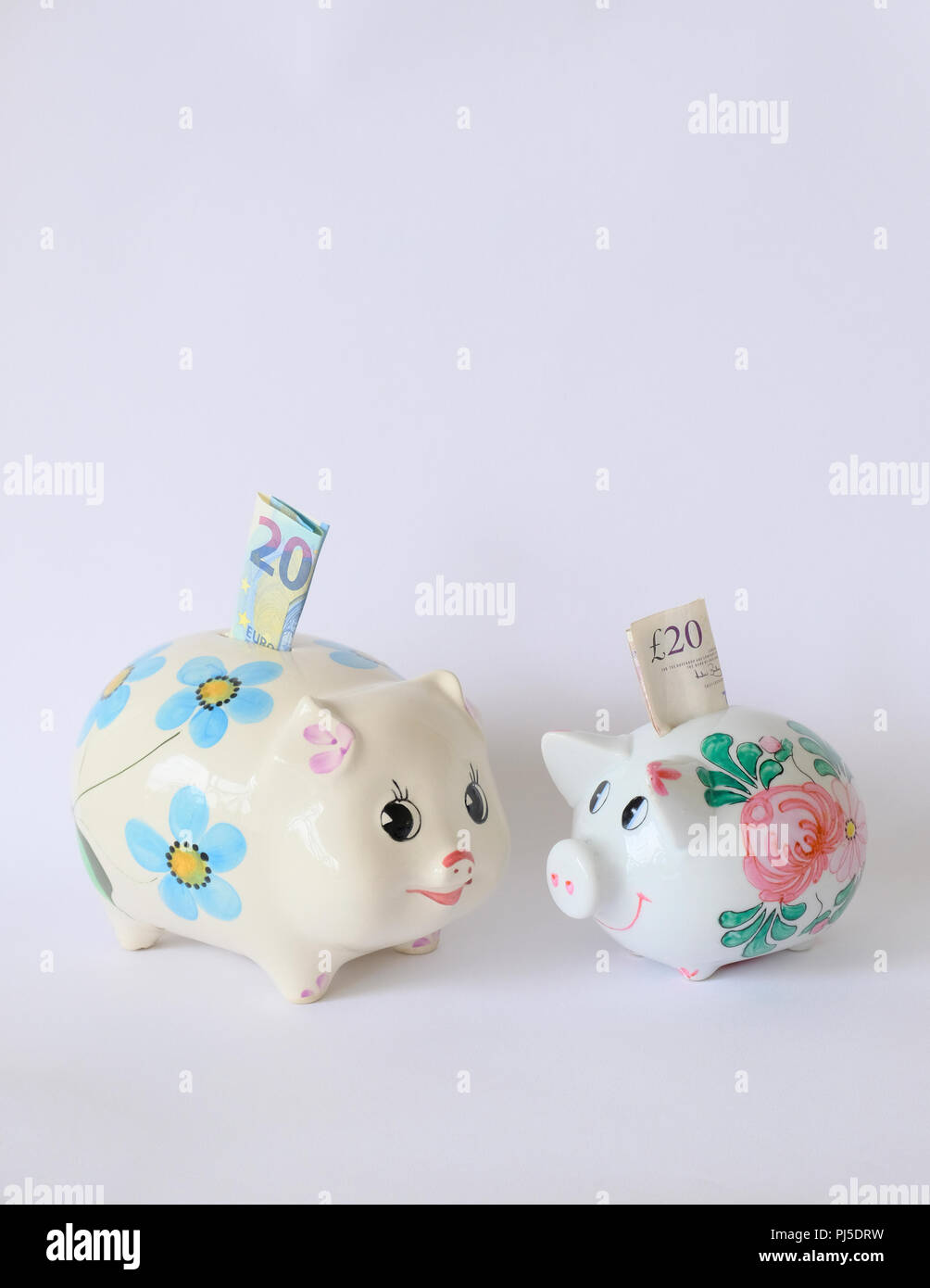 Pair of china piggy banks the larger with a 20 Euro note and the smaller with a 20 pound note - Stock Image