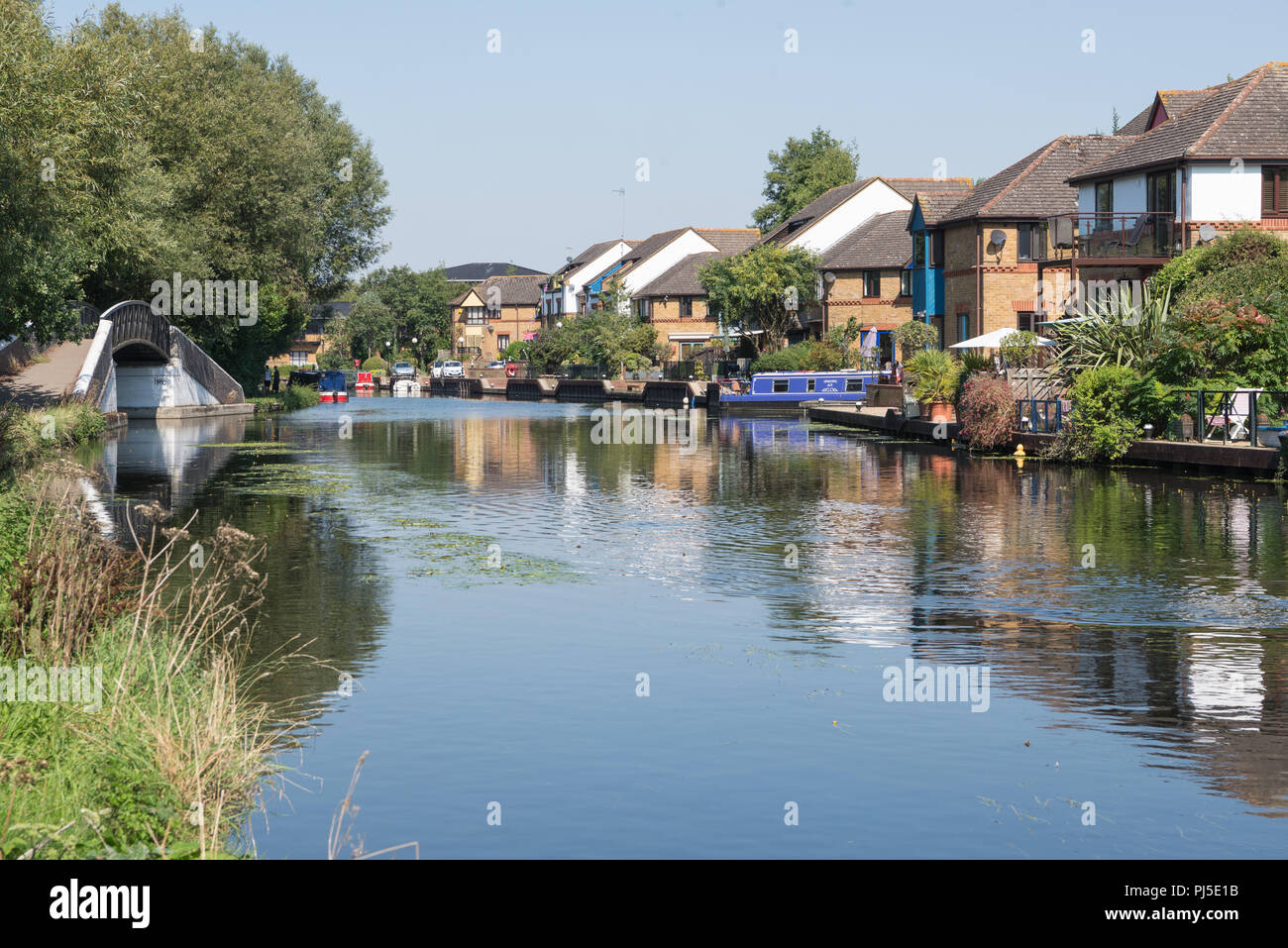 View from the towpath looking north along the Grand Union Canal. Attractive modern houses line the waterfront. Harefield, Middlesex, England, UK - Stock Image