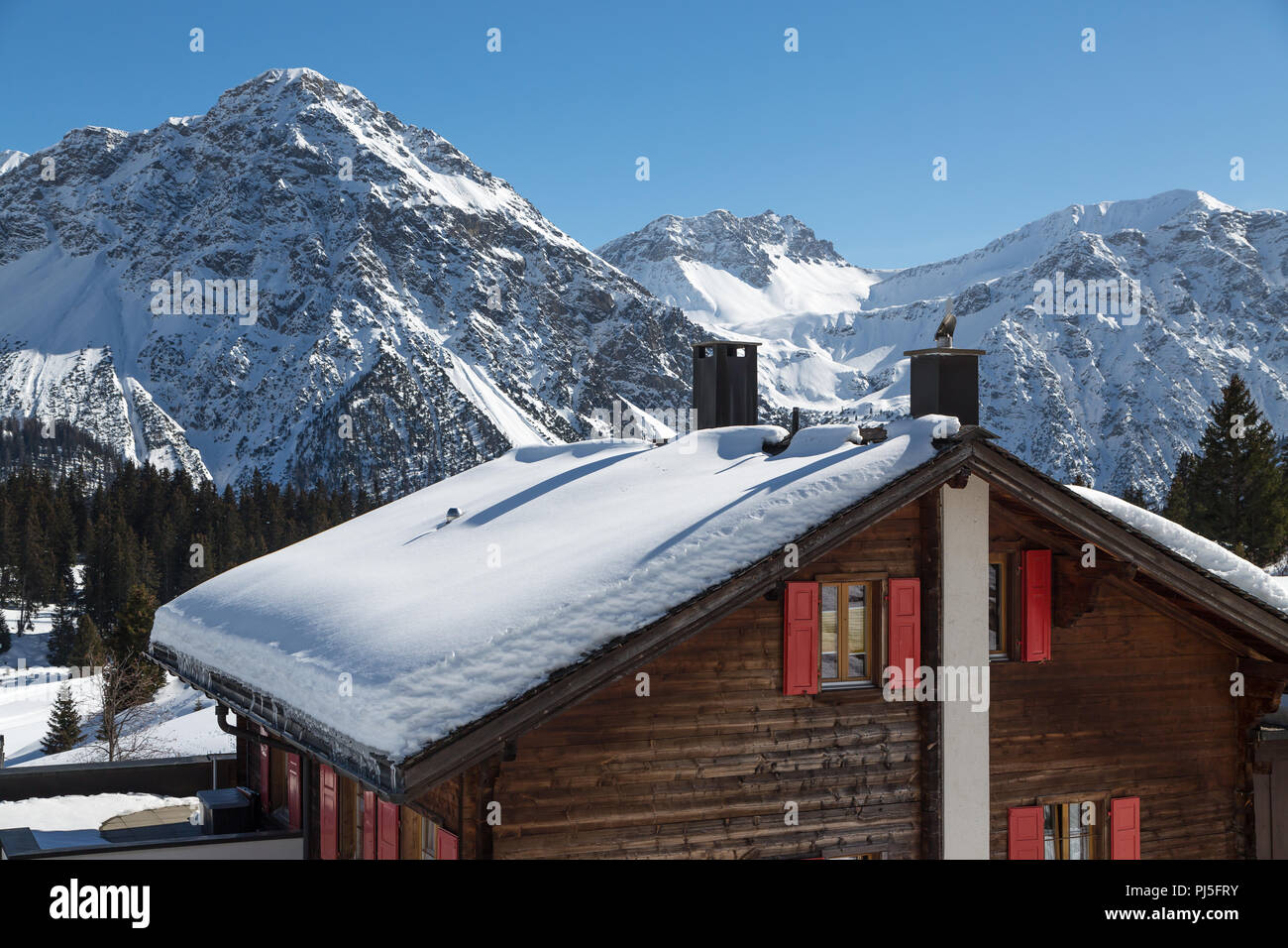 Woodhouse with snowy roof in Arosa Stock Photo