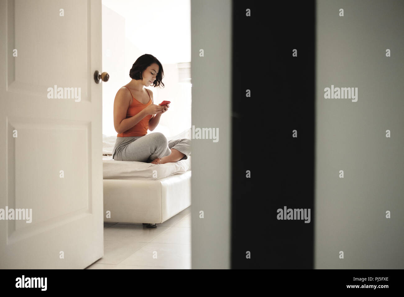 Hispanic woman sitting in bed at home with smart phone. Girl addicted to social media, checking her account on mobile phone in bedroom at morning. - Stock Image