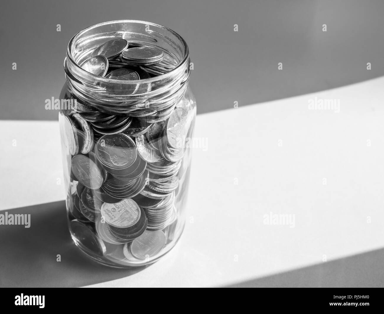 Coins in glass jar isolated on blue background with copy space in black and white style. Saving money concept. - Stock Image