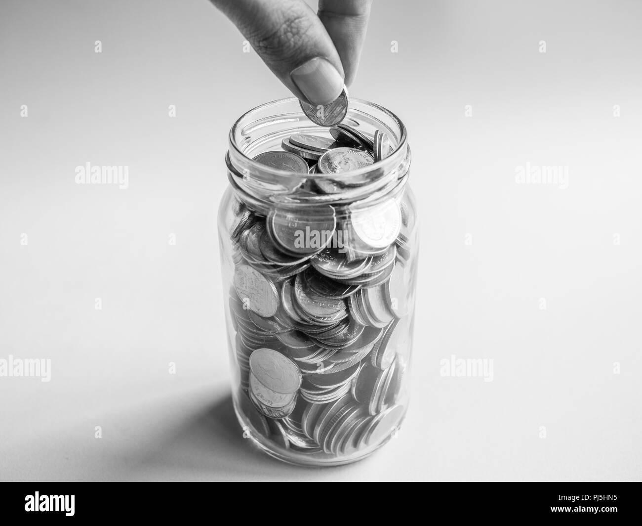 Hand holding coins in glass jar isolated on blue background in black and white style. Saving money concept. - Stock Image