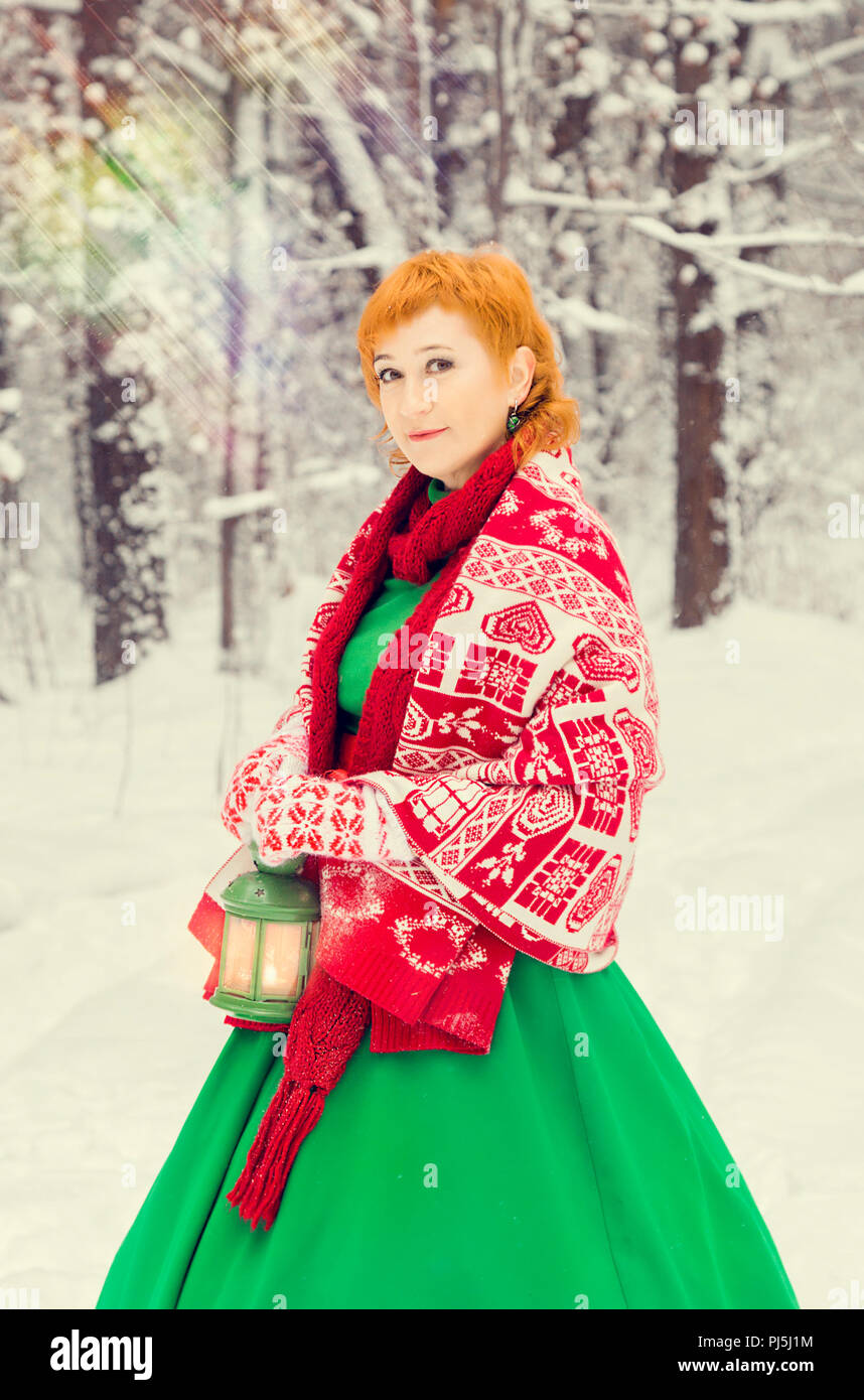 fiery red-haired woman in a ball green dress with a red leather belt in the costume of dwarf assistant Santa Claus in the winter forest with huge cand Stock Photo