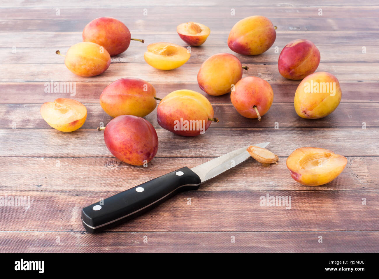 Whole and halved British Victoria plums on dark brown rustic wood panel background. Stock Photo