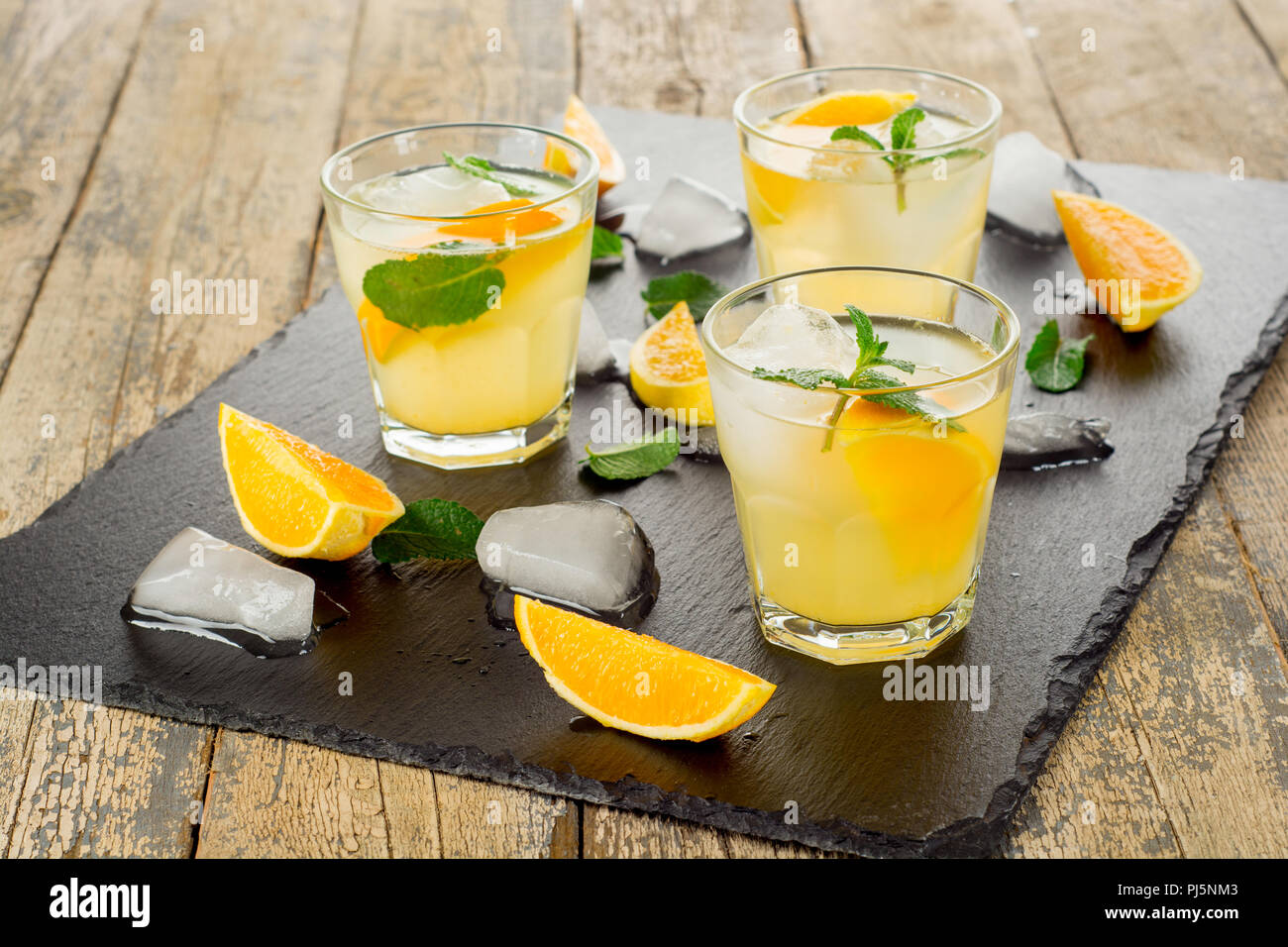 Summer drink. Citrus lemonade with mint and ice on white wooden background. - Stock Image