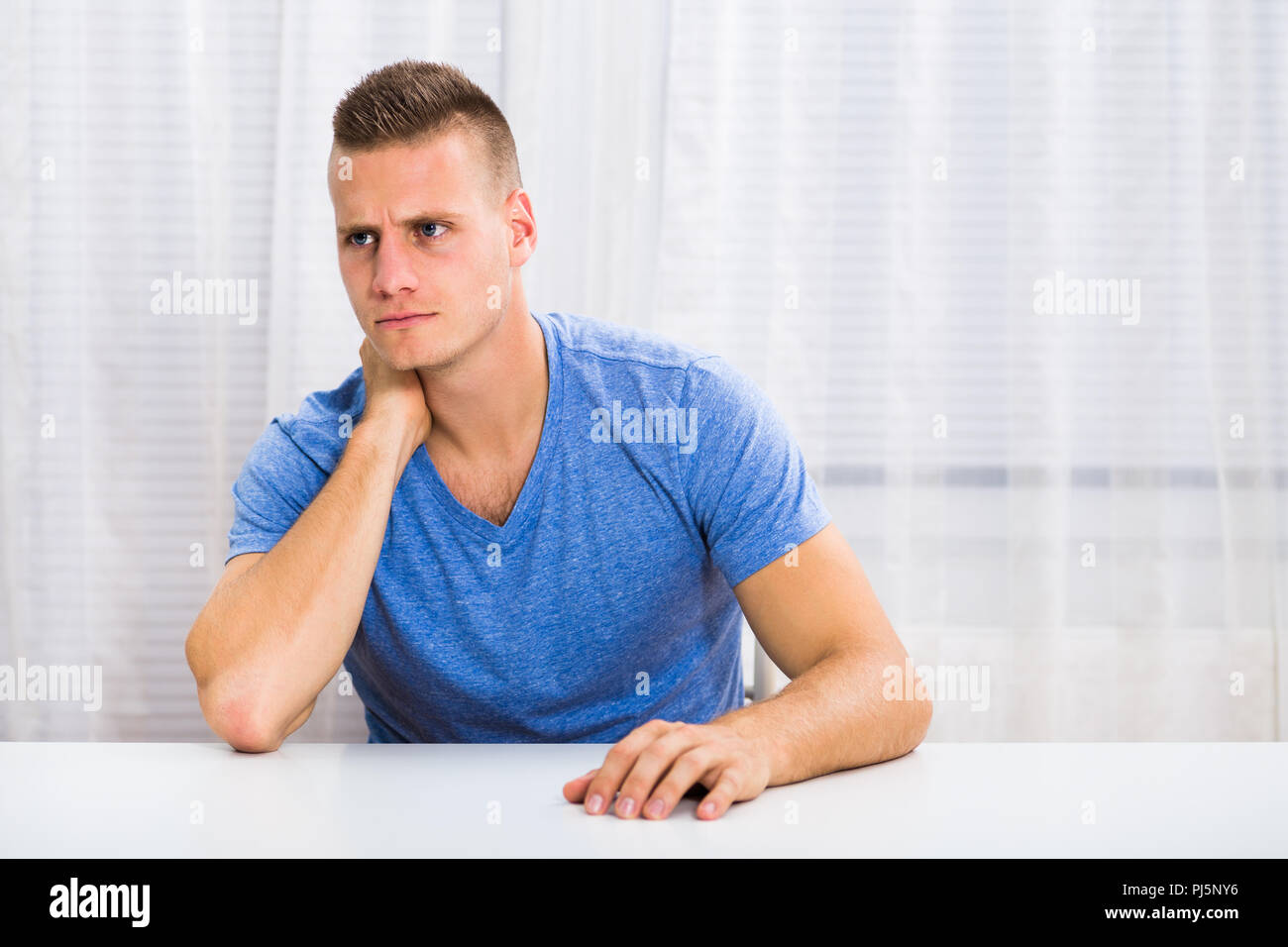 Young man is having neck pain. - Stock Image