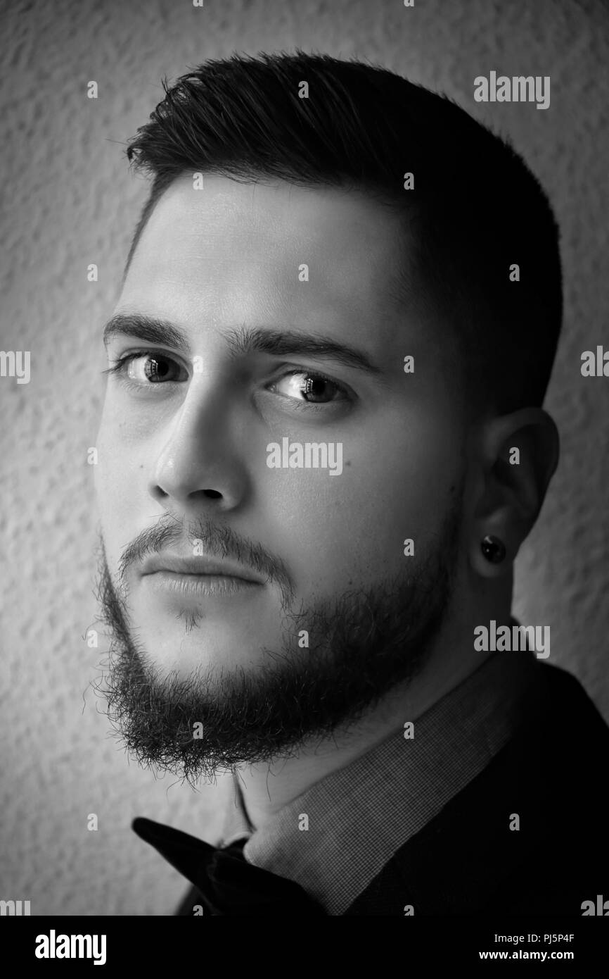 Black and white portrait of a handsome boy with a beard dressed smartly - Stock Image