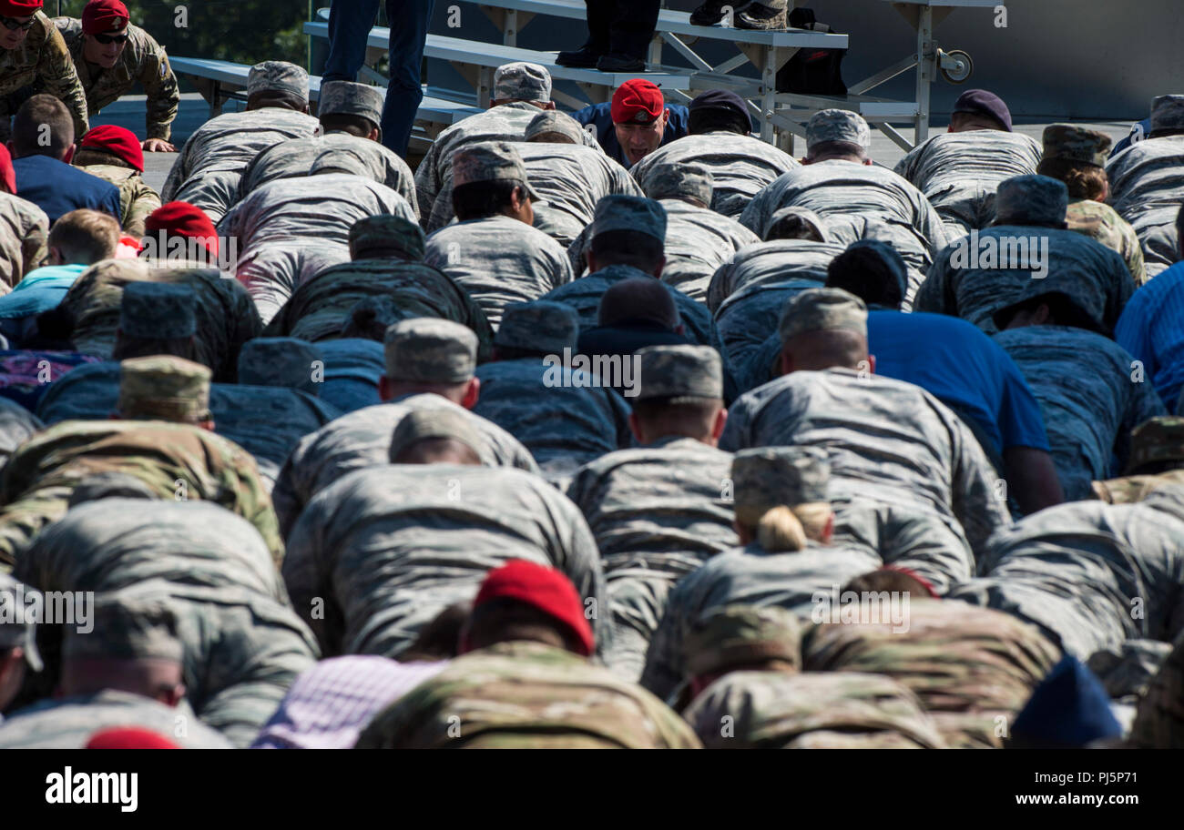 Attendees participate in memorial push-ups during Tech. Sgt. John Chapman's name unveiling ceremony at the Air Force Memorial, in Arlington, Va., Aug. 24, 2018. Chapman was posthumously awarded the Medal of Honor for actions on Takur Ghar mountain in Afghanistan on March 4, 2002. An elite special operations team was ambushed by the enemy and came under heavy fire from multiple directions. Chapman immediately charged an enemy bunker through high-deep snow and killed all enemy occupants. Courageously moving from cover to assault a second machine gun bunker, he was injured by enemy fire. Despite  Stock Photo