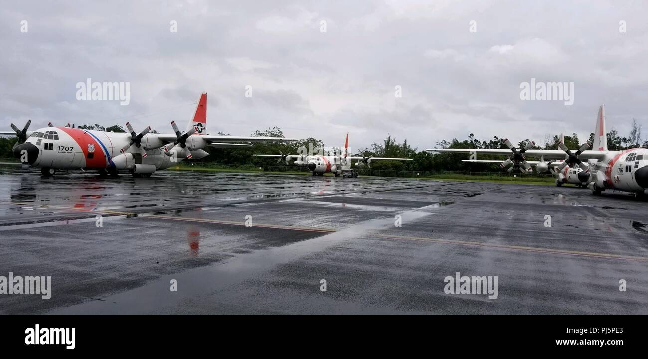 Air Station Barbers Point HC-130 Hercules aircraft await tasking in response to Hurricane Lane at Hilo International Airport, Hawaii, Aug. 24, 2018. The Coast Guard was working closely with federal, state and local authorities to prepare for Hurricane Lane. (U.S. Coast Guard photo by Chief Petty Officer Billy Mapakoi/Released) - Stock Image