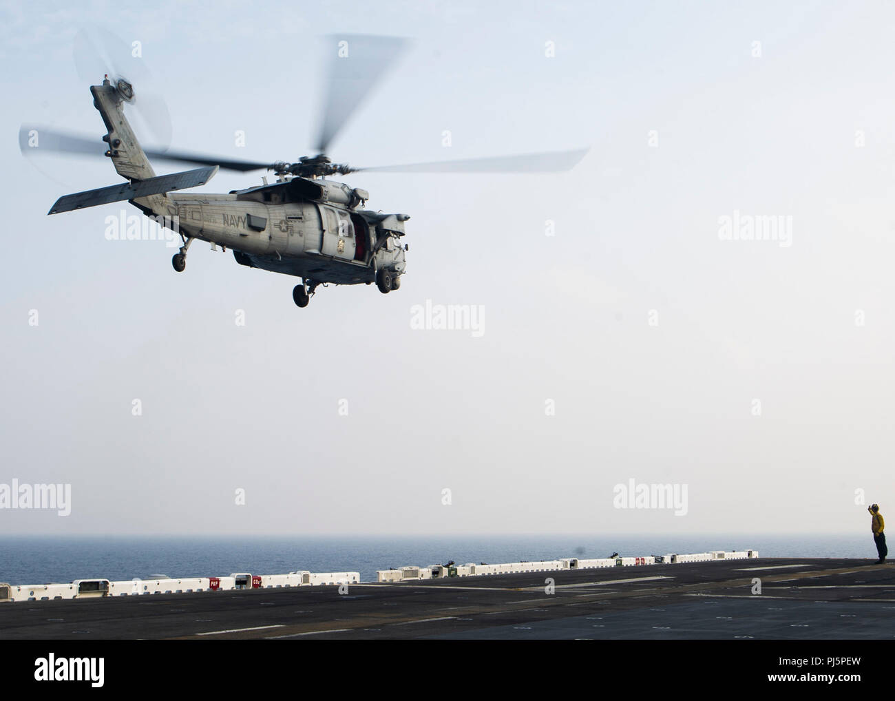 """180824-N-NB142-0477  SOUTH CHINA SEA (Aug. 24, 2018) – An MH-60S Sea Hawk helicopter, attached to the """"Blackjacks"""" of Helicopter Sea Combat Squadron (HSC) 21, launches from the flight deck of Wasp-class amphibious assault ship USS Essex (LHD 2) during a regularly scheduled deployment of the Essex Amphibious Ready Group (ARG) and 13th Marine Expeditionary Unit (MEU). The Essex ARG/13th MEU is a capable and lethal Navy-Marine Corps team deployed to the 7th fleet area of operations to support regional stability, reassure partners and allies and maintain a presence postured to respond to any crisi - Stock Image"""