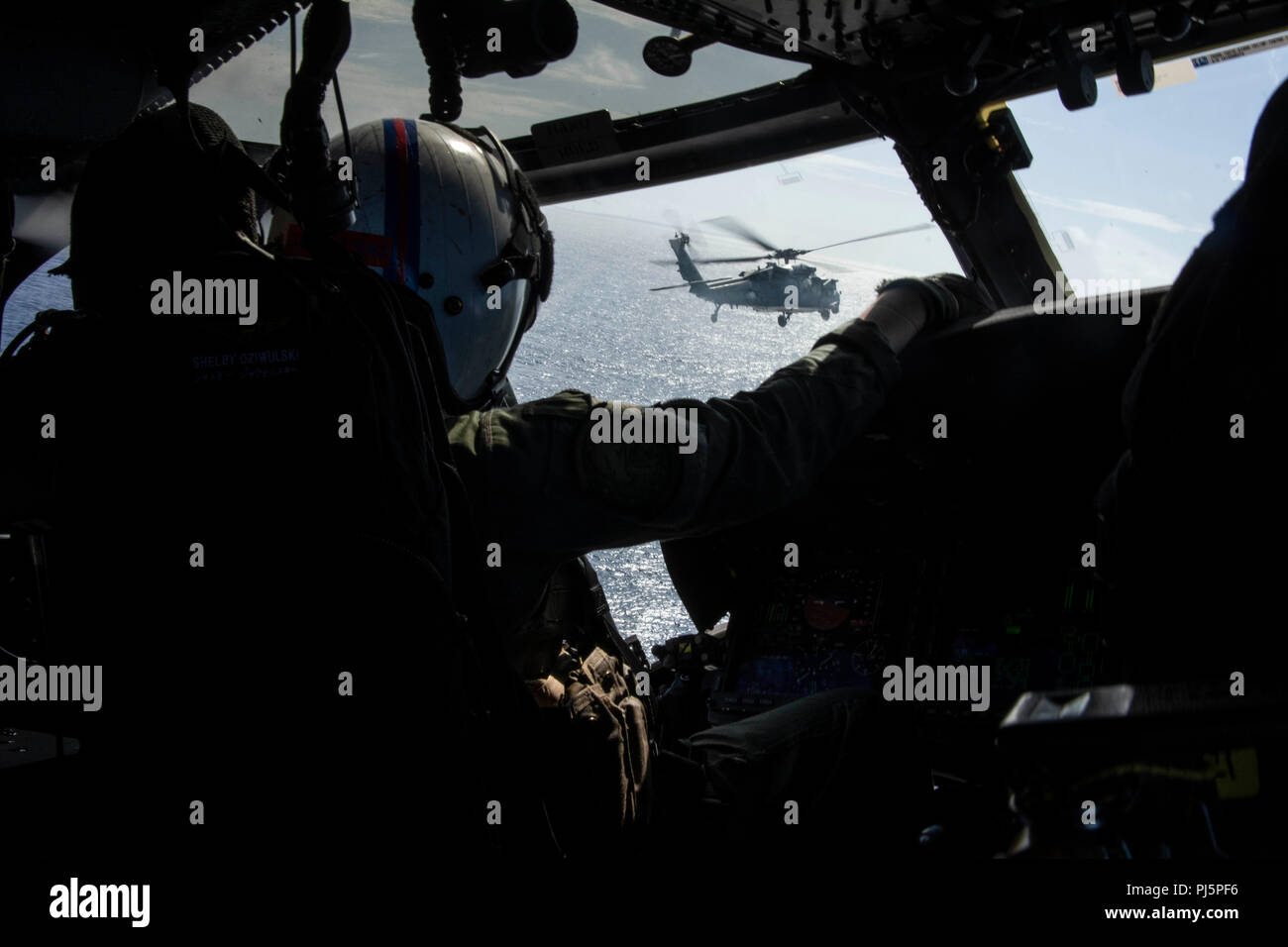 180824-N-VI515-0258  WATERS SOUTH OF JAPAN (Aug. 24, 2018) Lt. Shelby Dziwulski, from Baltimore, copilots an MH-60S Sea Hawk helicopter assigned to the Golden Eagles of Helicopter Sea Combat Squadron (HSC) 12. The squadron is embarked aboard the aircraft carrier USS Ronald Reagan (CVN 76), the flagship of Carrier Strike Group 5, which provides a combat-ready force that protects and defends the collective maritime interests of its allies and partners in the Indo-Pacific region. (U.S. Navy photo by Mass Communication Specialist 3rd Class Erwin Jacob V. Miciano/Released) Stock Photo