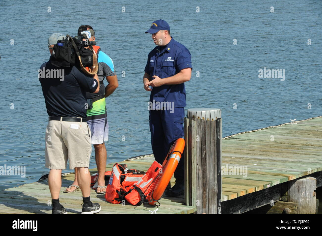 Coast Guard Petty Officer 1st Class William Campbell, the executive petty officer for the Cutter Razorbill, explains the different types of life jacket types to Walter Hilderbrand, a photojournalist at WAVY News 10, during a life jacket demonstration August 24, 2018, in Portsmouth, Virginia. Campbell also explained the fives different types of personal flotation devices that are available to all mariners, and how to properly use them in emergency situations. (U.S. Coast Guard photo by Petty Officer 3rd Class Shannon Kearney/Released) Stock Photo