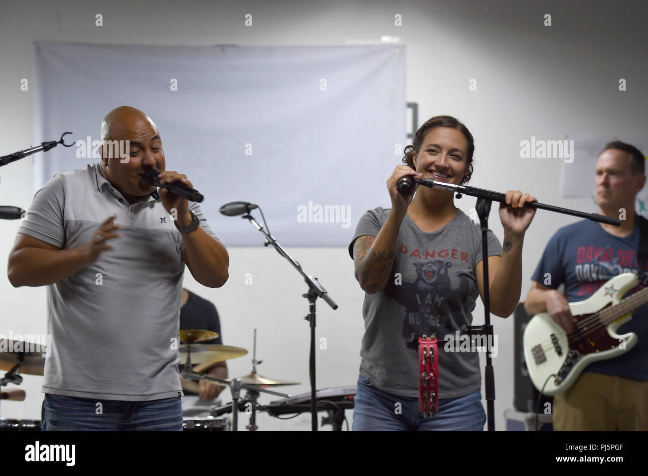 Master Sgt. Quez Vasquez and Staff Sgt. Grace Huntoon, U.S. Air Forces Central Command Band lead vocalists, perform for deployed service members at an undisclosed location in Southwest Asia, Aug. 24, 2018. The USAFCENT Band rotates several ensembles through the area of responsibility that perform a wide variety of musical styles to appeal to audiences of all ages and backgrounds. (U.S. Air Force photo by Staff Sgt. Dana J. Cable) - Stock Image