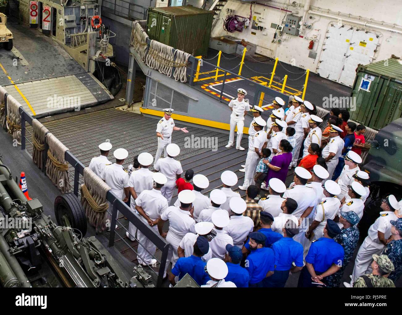 180825-N-PH222-0142 TRINCOMALEE, SRI LANKA (Aug. 25, 2018) Capt. Dennis Jacko, commanding officer of San Antonio-class amphibious transport dock USS Anchorage (LPD 23), from Sayreville, N.J., gives a tour of the well deck to distinguished visitors of the Sri Lanka navy and their families during a regularly scheduled deployment of the Essex Amphibious Ready Group (ARG) and 13th Marine Expeditionary Unit (MEU). Anchorage and the embarked Marines of the 13th MEU are conducting a theater security cooperation exercise with the Sri Lankan navy and marines. Part of a growing U.S.-Sri Lanka naval part - Stock Image