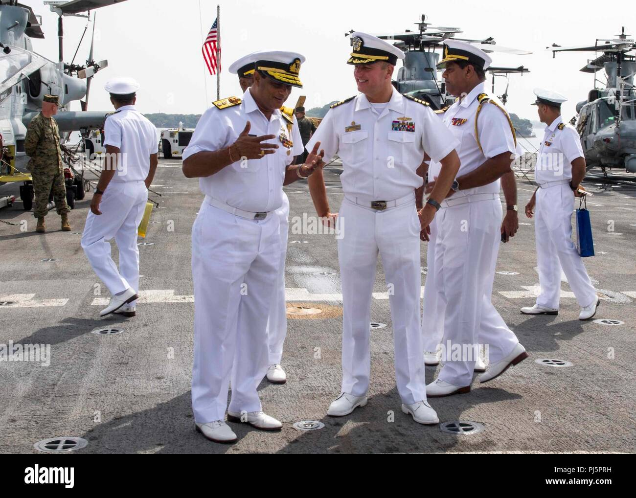 180825-N-PH222-0308 TRINCOMALEE, SRI LANKA (Aug. 25, 2018) Capt. Dennis Jacko, commanding officer of San Antonio-class amphibious transport dock USS Anchorage (LPD 23), from Sayreville, N.J., talks with Sri Lanka navy Rear Adm. SA Weerasinghe, commander, East Naval Forces, during a tour of the flight deck while on a regularly scheduled deployment of the Essex Amphibious Ready Group (ARG) and 13th Marine Expeditionary Unit (MEU). Anchorage and the embarked Marines of the 13th MEU are conducting a theater security cooperation exercise with the Sri Lankan navy and marines. Part of a growing U.S.- - Stock Image
