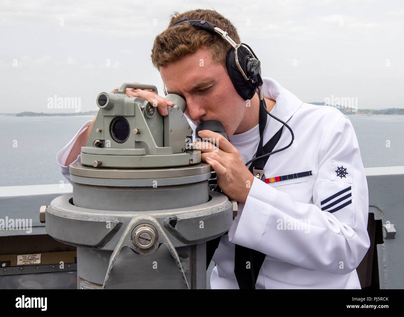 180824-N-PH222-0114 TRINCOMALEE, SRI LANKA (August 24, 2018) Quartermaster Seaman Keegan Taylor, from Houston, takes a bearing during a sea and anchor detail on the bridge wing of San Antonio-class amphibious transport dock USS Anchorage (LPD 23) before a scheduled port visit in Trincomalee, Sri Lanka, during a regularly scheduled deployment of the Essex Amphibious Ready Group (ARG) and 13th Marine Expeditionary Unit (MEU). Anchorage and the embarked Marines of the 13th MEU are conducting a theater security cooperation exercise with the Sri Lankan Navy and the Navy Marines. Part of a growing U - Stock Image
