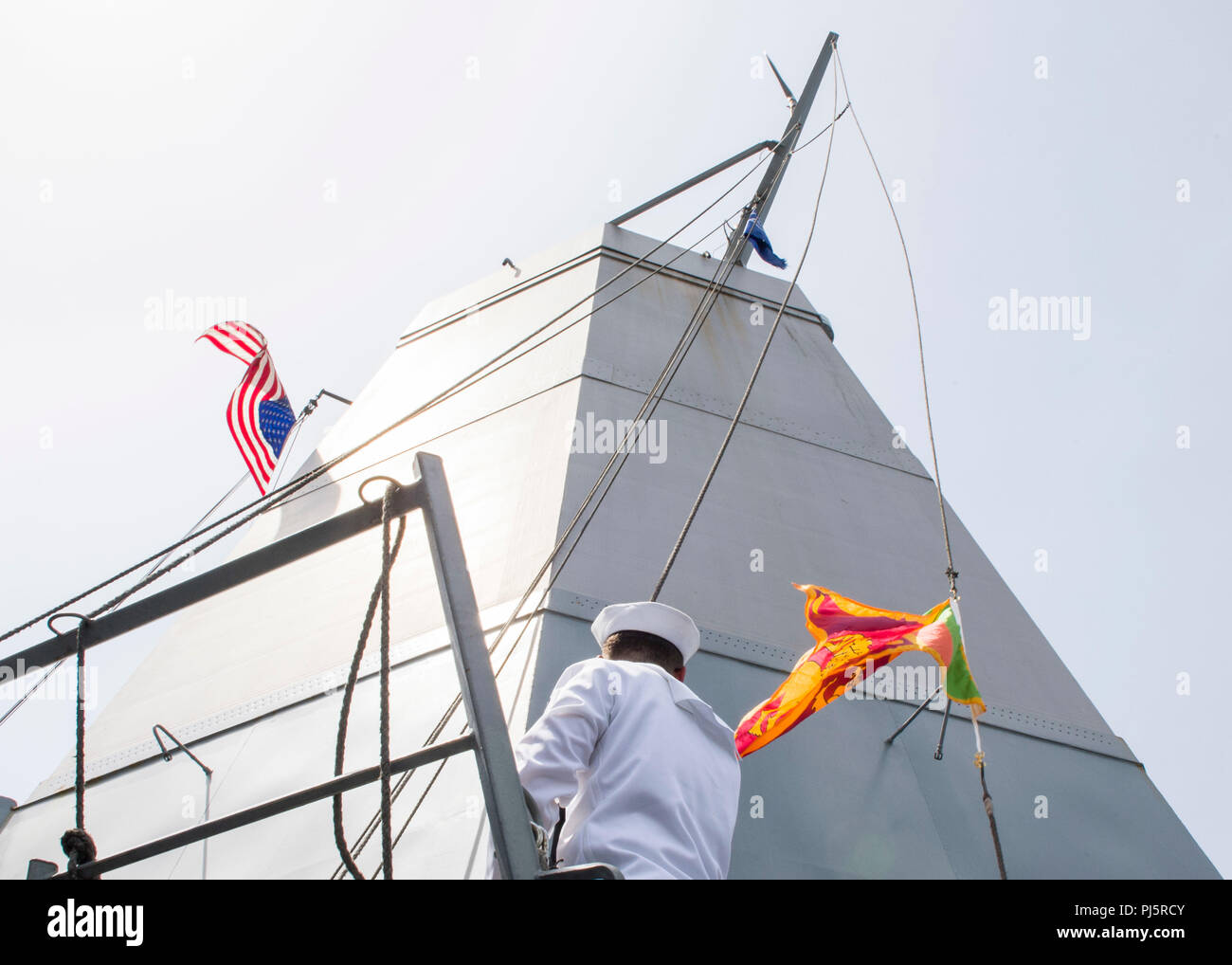 180824-N-PH222-0441 TRINCOMALEE, SRI LANKA (August 24, 2018) Quartermaster 2nd Class Brandon Sassone, from Plainview, N.Y., hoists the Sri Lankan nation flag from the bridge wing of San Antonio-class amphibious transport dock USS Anchorage (LPD 23) before a scheduled port visit in Trincomalee, Sri Lanka during a regularly scheduled deployment of the Essex Amphibious Ready Group (ARG) and 13th Marine Expeditionary Unit (MEU). Anchorage and the embarked Marines of the 13th MEU are conducting a theater security cooperation exercise with the Sri Lankan Navy and the Navy Marines. Part of a growing  - Stock Image