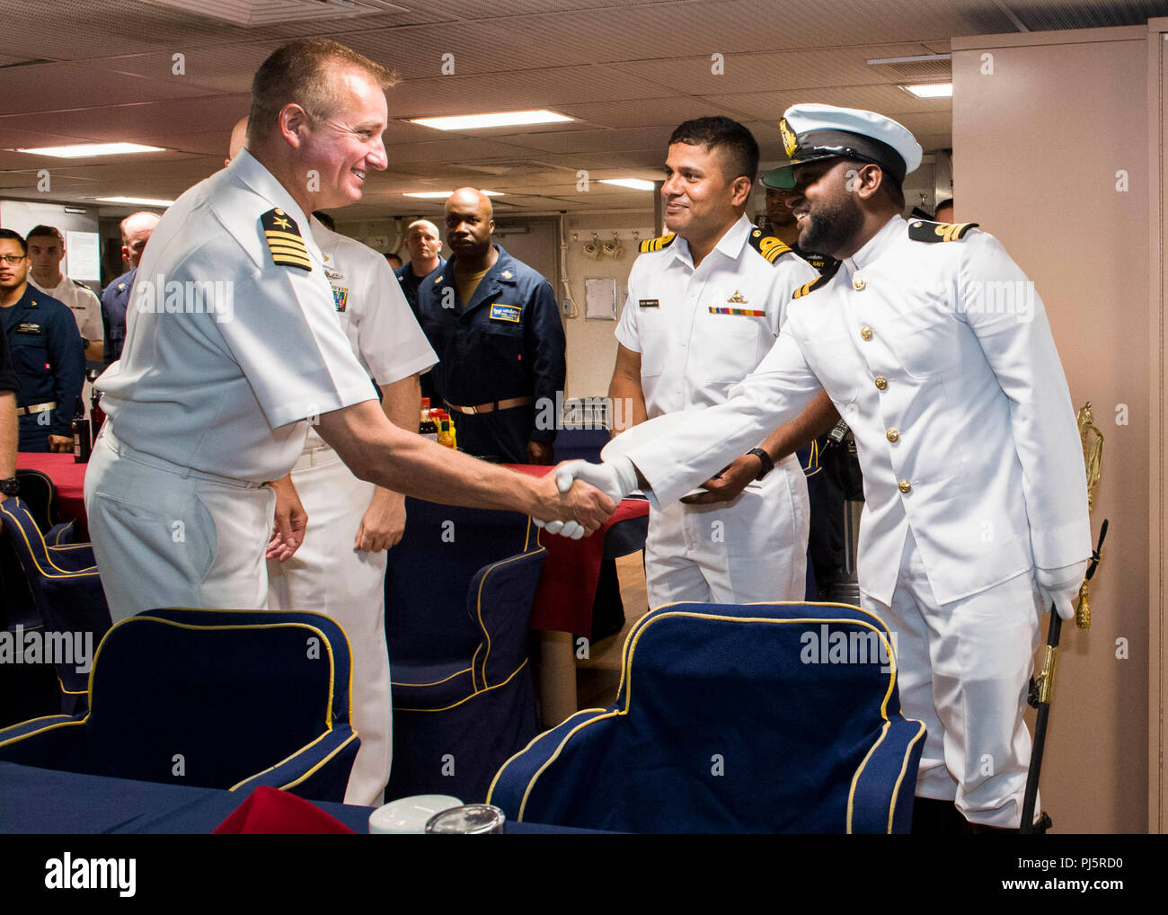180824-N-PH222-0574 TRINCOMALEE, SRI LANKA (August 24, 2018) Capt. Dennis Jacko, from Sayreville, N.J., commanding officer of San Antonio-class amphibious transport dock USS Anchorage (LPD 23) greets Sri Lankan Navy officials in the wardroom during a scheduled port visit in Trincomalee, Sri Lanka during a regularly scheduled deployment of the Essex Amphibious Ready Group (ARG) and 13th Marine Expeditionary Unit (MEU). Anchorage and the embarked Marines of the 13th MEU are conducting a theater security cooperation exercise with the Sri Lankan Navy and the Navy Marines. Part of a growing U.S.-Sr - Stock Image