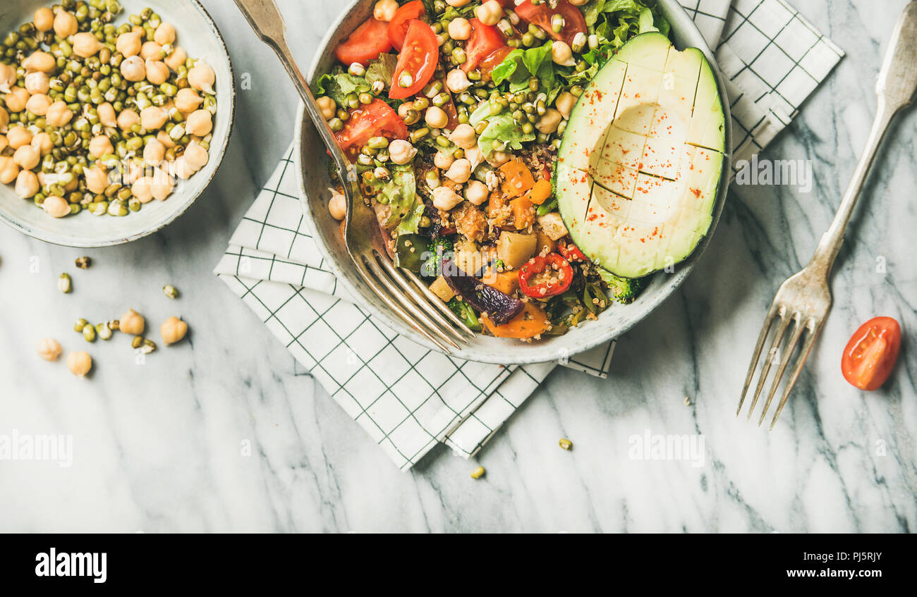 Vegan lunch bowl. Flat-lay of dinner with avocado, grains, beans, sprouts, greens and vegetables over marble background, top view, copy space, close-u - Stock Image