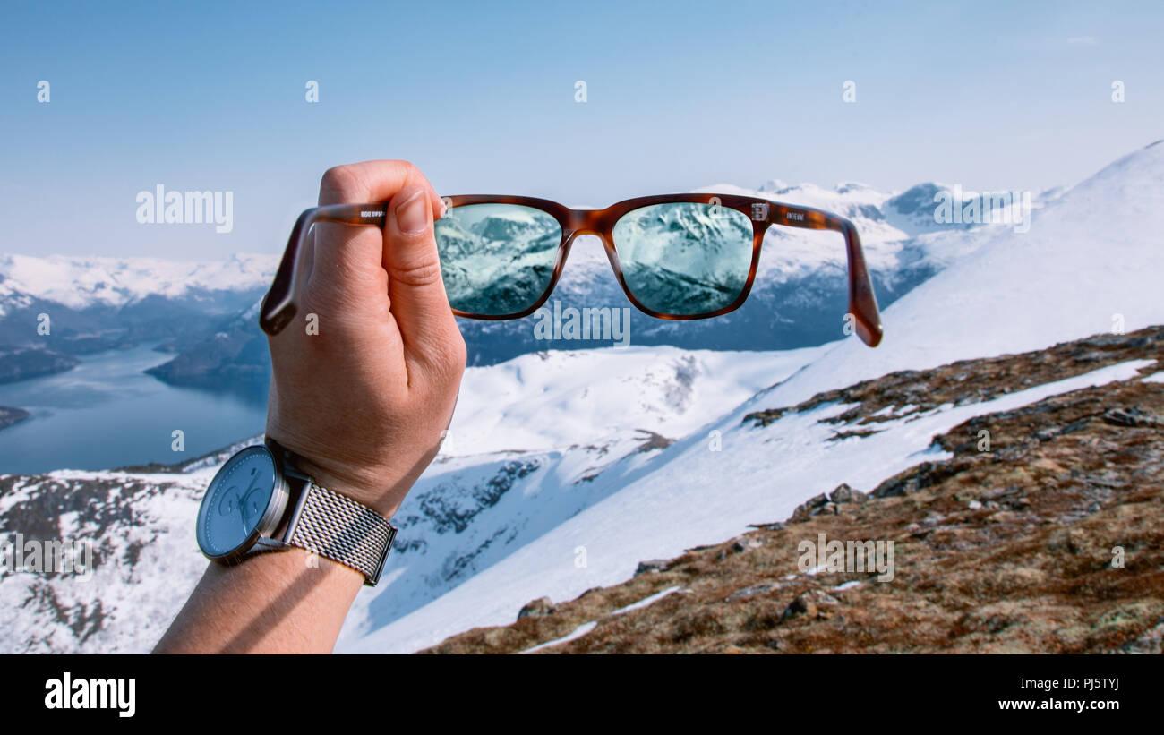 Norwegian mountain range in Volda as seen through a hiker's sunglasses. - Stock Image