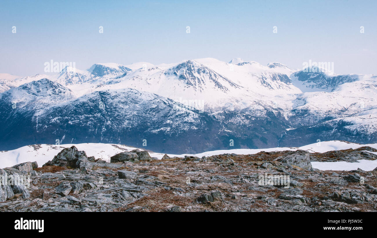 Snow covered mountain range in Volda Norway as seen from another mountain - Stock Image
