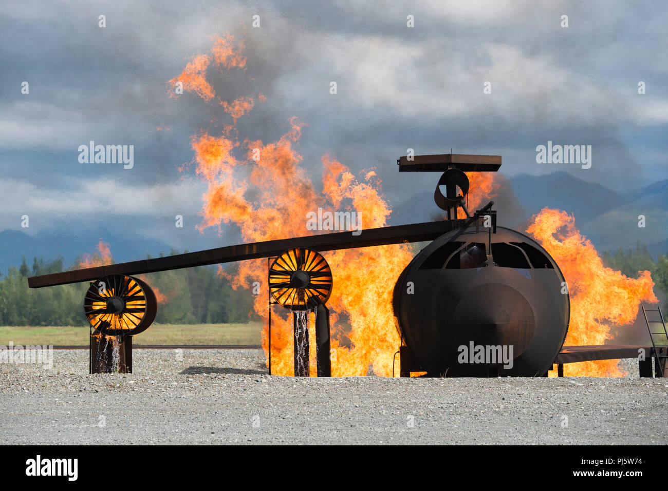 An aircraft fire training simulator is engulfed in flames