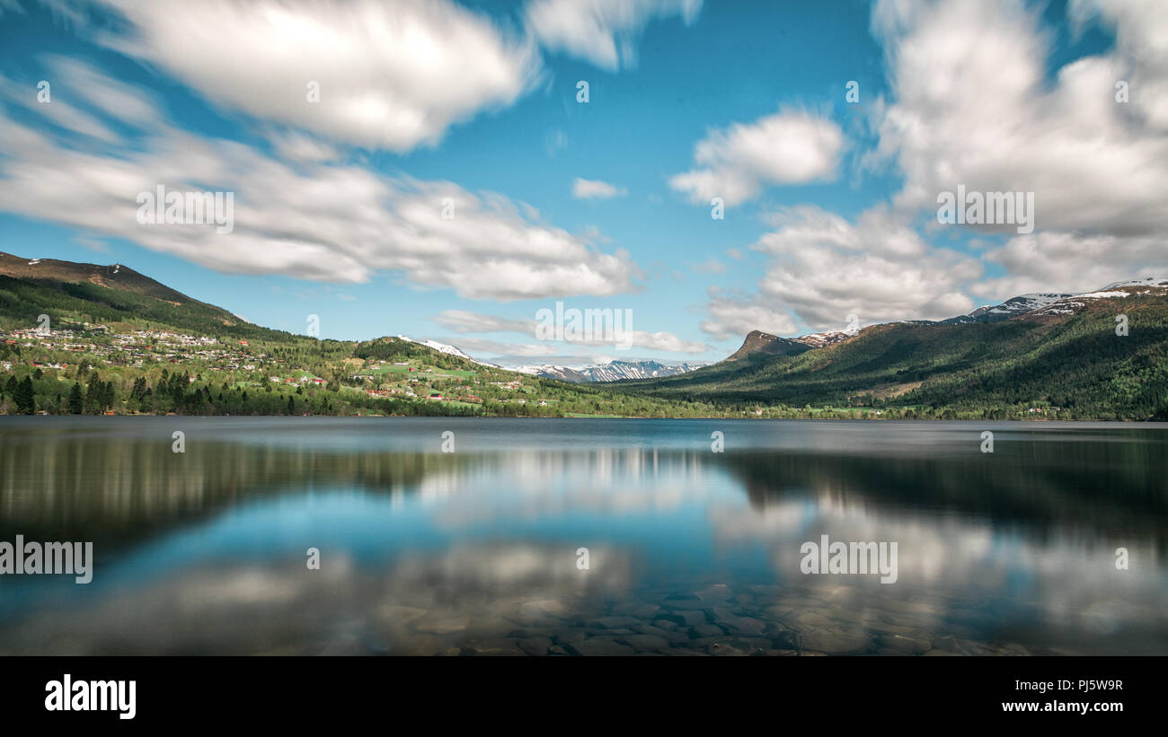Reflections in like of blue skies and clouds in Volda Norway - Stock Image