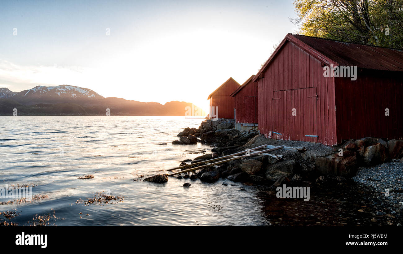 Three red boathouses on the fjord in Volda Norway - Stock Image