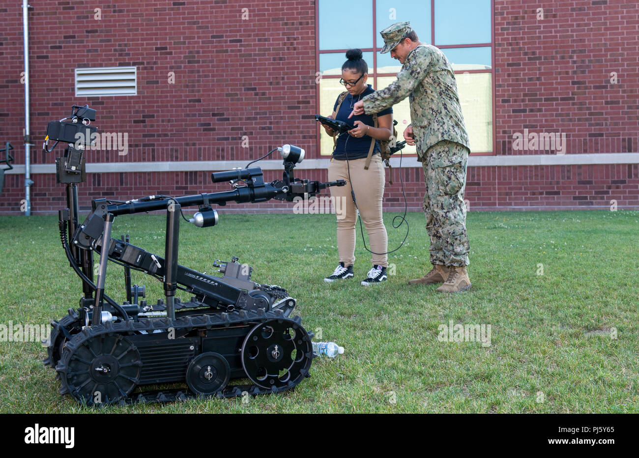180828-N-RJ834-037  CLEVELAND (Aug. 28, 2018) Navy Diver 1st Class Erik Clark, from Ashland, N.C., attached to Mobile Diving and Salvage Unit (MDSU) 2, demonstrates the operation of an explosive ordinance disposal robot to John Marshall School of Engineering High School students during Cleveland Navy Week in Cleveland, Ohio. The Navy Office of Community Outreach uses the Navy Week program to bring Navy Sailors, equipment and displays to approximately 14 American cities each year for a week-long schedule of outreach engagements designed for Americans to experience firsthand how the U.S. Navy is Stock Photo