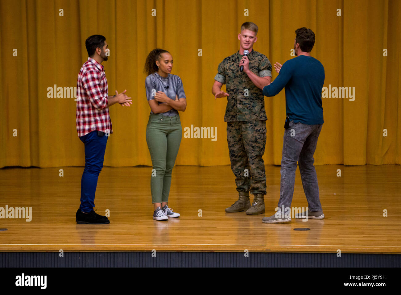 CAMP FOSTER, OKINAWA, Japan— Lance Cpl. Jonah Edwards (center right) participates in an improvised acting exercise during the Pure Praxis Sexual Assault Prevention and Response Performance Education Workshop Aug. 28 at the theater on Camp Foster, Okinawa, Japan. Marines and sailors from the audience acted out scenarios with the Pure Praxis actors on the stage. Edwards is a personnel clerk with Headquarters and Support Battalion, Marine Corps Installations Pacific. (U.S. Marine Corps photo by Lance Cpl. Brennan Priest) Stock Photo