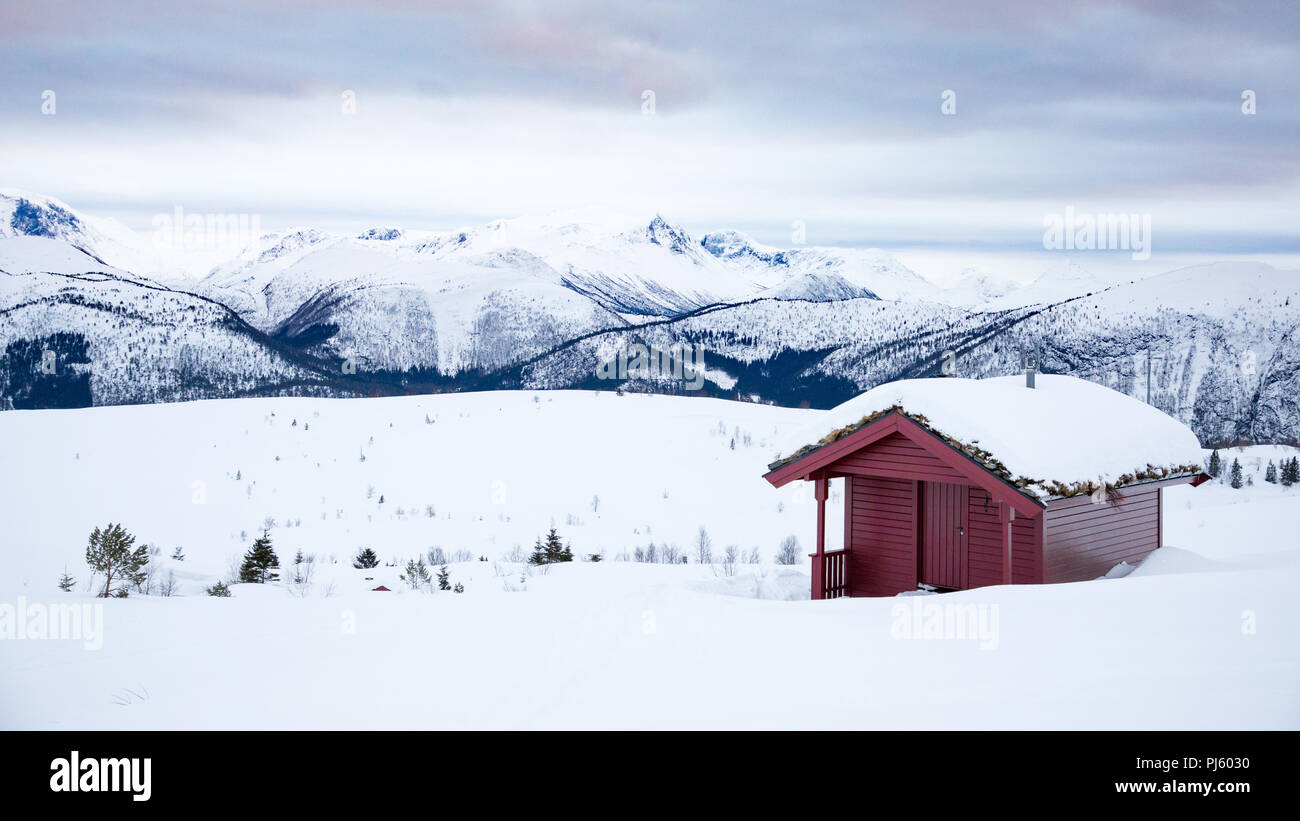 Red cabin on snow covered mountain in Volda Norway - Stock Image