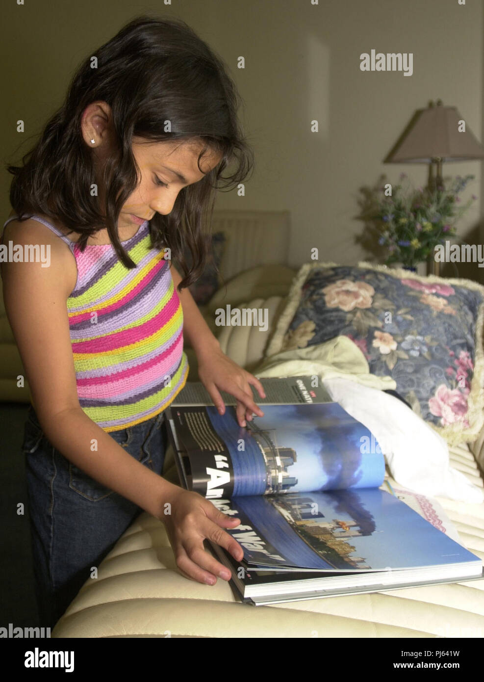 Chantal Guerrero, who will be 8 on August 20, 2002, looks through a life magazine book on September 11. She pauses on a picture of the burning World Trade Center Towers. Chantal was in the class with President Bush when he found out about the terrorist act.  Almost one year after September 11th, the class of Mrs. Daniels meets again, interviews the night before the first day of school.  July 30, 2002. (Jessica Mann/Orlando Sentinel) - Stock Image