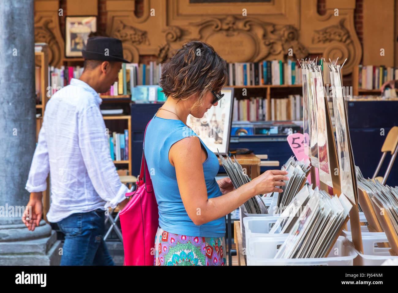 Woman shopping in the old book and antiques market, held in Vielle Bourse de Lille, Place du General de Gaulle, Lille, France - Stock Image