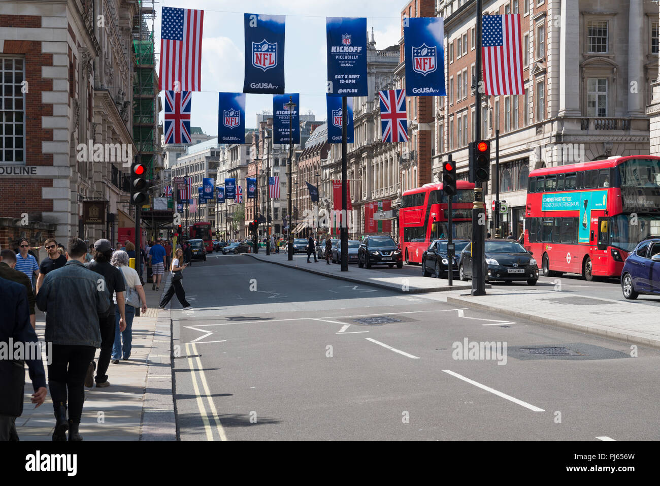 Busy street scene in Piccadilly, London. Advertising banners for the NFL and British and American flags hang above the street. England, UK - Stock Image