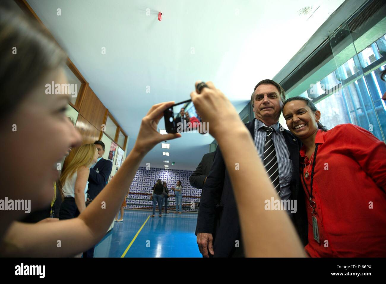 Brasilia, Brazil. 04th Sep, 2018. A supporter takes a picture with Brazilian Presidential Candidate Jair Bolsonaro (PSL) (2-R) in the corridors of the National Congress building, in Brasilia, Brazil, 04 September 2018. The Brazilian presidential election will take place on 07 October 2018. Credit: Joedson Alves/EFE/Alamy Live News - Stock Image