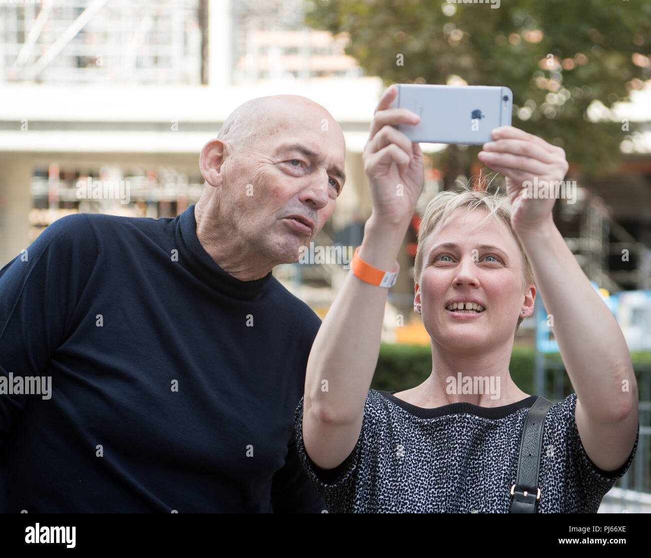 Berlin, Germany. 04th Sep, 2018. 04.09.2018, Berlin: The architects Rem Koohlhaas (l) and Katrin Betschinger from the architectural office Office for Metropolitan Architecture (OMA) take pictures with a smartphone during the topping-out ceremony for the Axel Springer new building. Credit: Soeren Stache/dpa/Alamy Live News - Stock Image