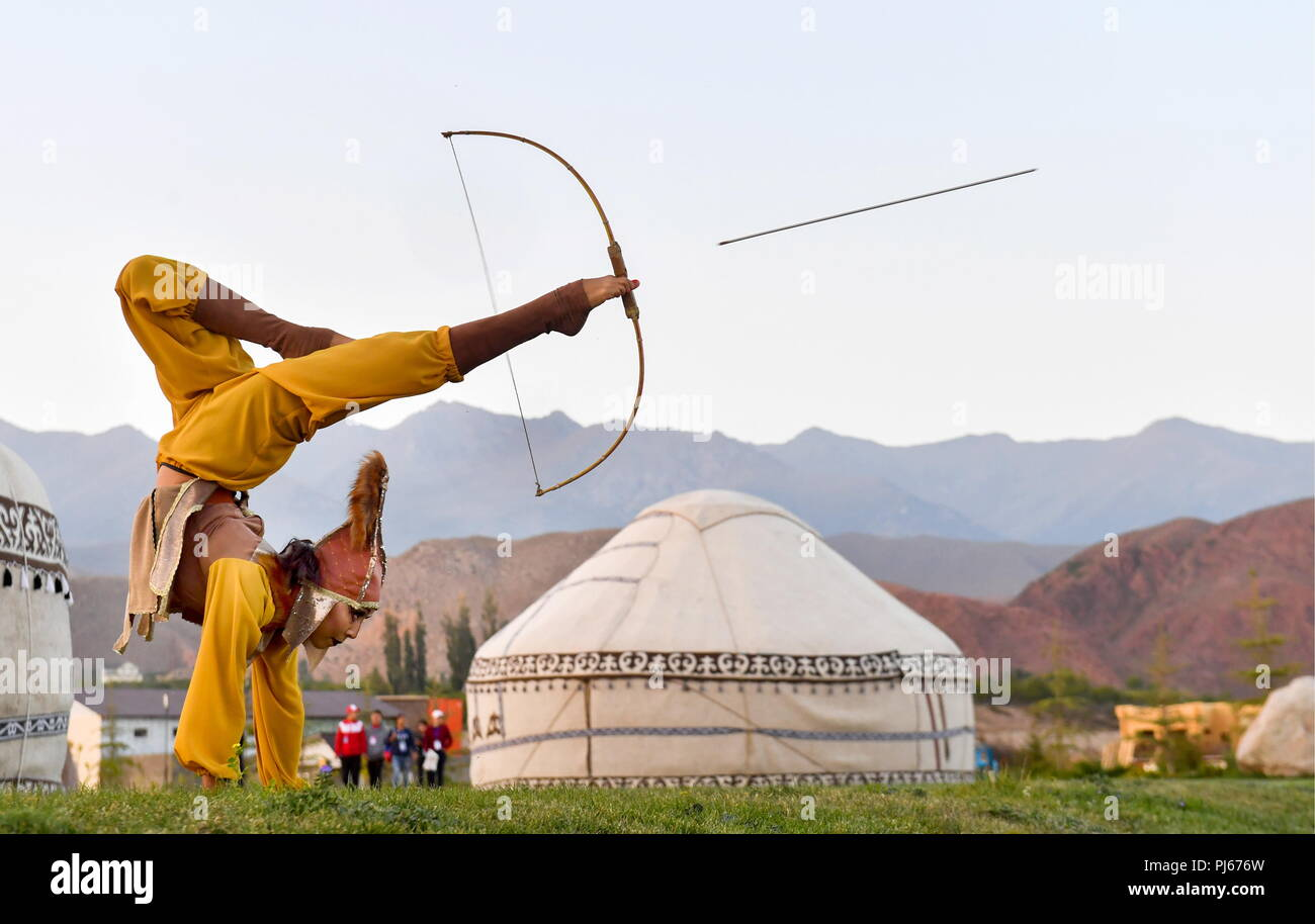 Kyrgyzstan. 04th Sep, 2018. ISSYK-KUL REGION, KYRGYZSTAN - SEPTEMBER 4, 2018: A woman shoots a bow and arrow with her feet at the 2018 World Nomad Games held in the town of Cholpon-Ata, Issyk-Kul Region, Kyrgyzstan, every two years and including 37 ethnic sporting events, such as horse riding, national wrestling, martial arts, traditional mind games, archery, hunting, etc. Viktor Drachev/TASS Credit: ITAR-TASS News Agency/Alamy Live News - Stock Image